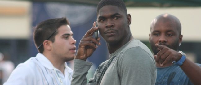 Keyshawn Johnson stands, head turned, as he speaks on the phone--photograph taken by paparazzi