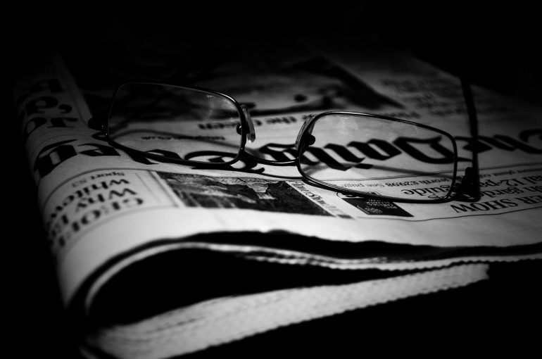 Black and white photograph of glasses sitting on a folded newspaper
