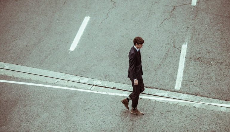 A person walking alone on a street, dressed in a suit