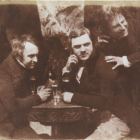 Old, sepia photograph of a group of three men drinking together at a table, one of the men is crouched behind in the other, and is in motion