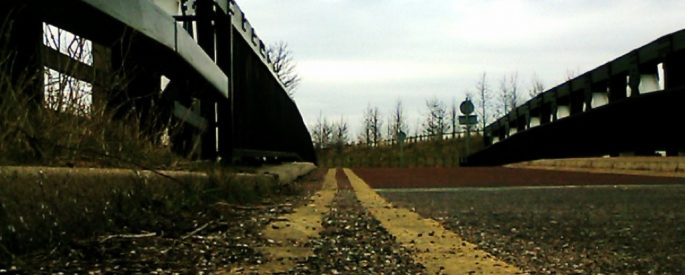 photo of what appears to be an abandoned industrial site--the photo draws the eye forward, towards the horizon down a long, unkempt road