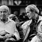 Two older men site on a bench in black and white.