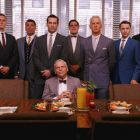 The main characters of Mad Men lined up behind a desk with one man seated at the desk