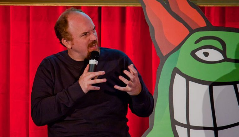 Comedian Louis CK on stage and looking to his left with his hands up
