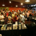 Crowd of people in bookstore with stacks of books to buy