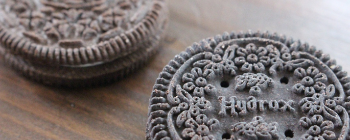 Two chocolate sandwich cookies, one an Oreo and one an off-brand, side by side.