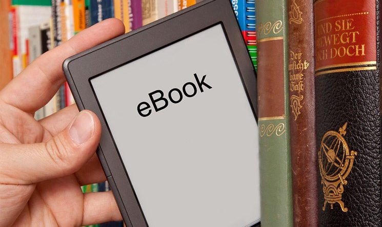 Hand drawing an e-reader from a bookshelf full of codices