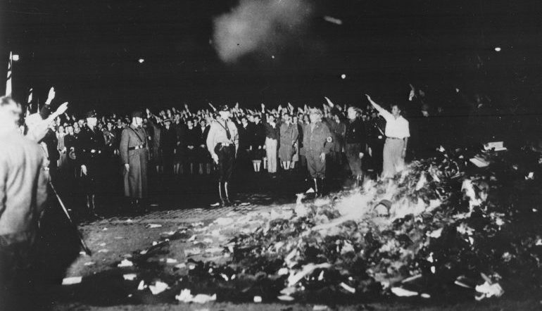 Black and white photo of a group of people burning a pile of books in the middle