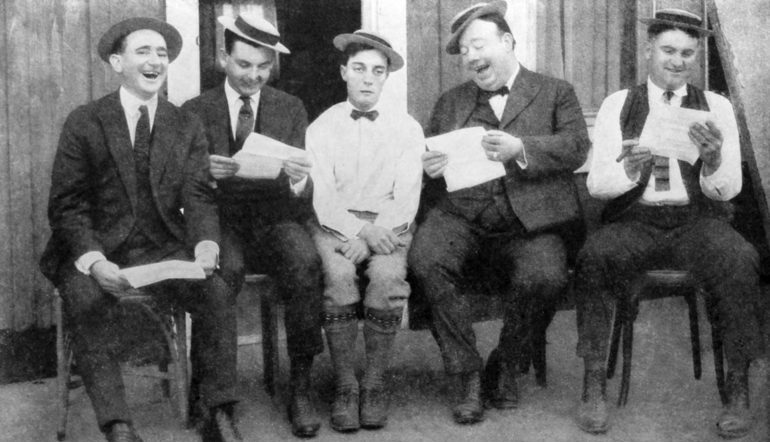 Group of 5 men, four of whom are laughing and writing, the one in the middle is stone faced