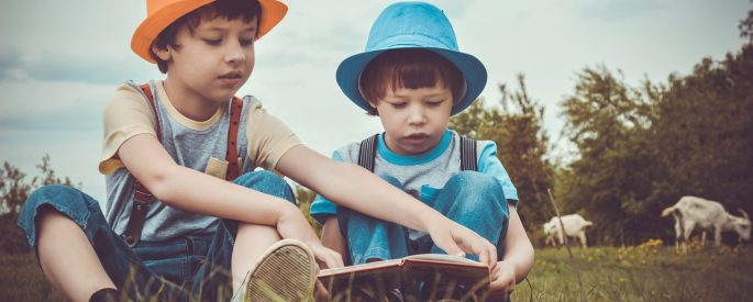 Two small children, one in an orange hat and one in a blue, sit reading in a meadow.