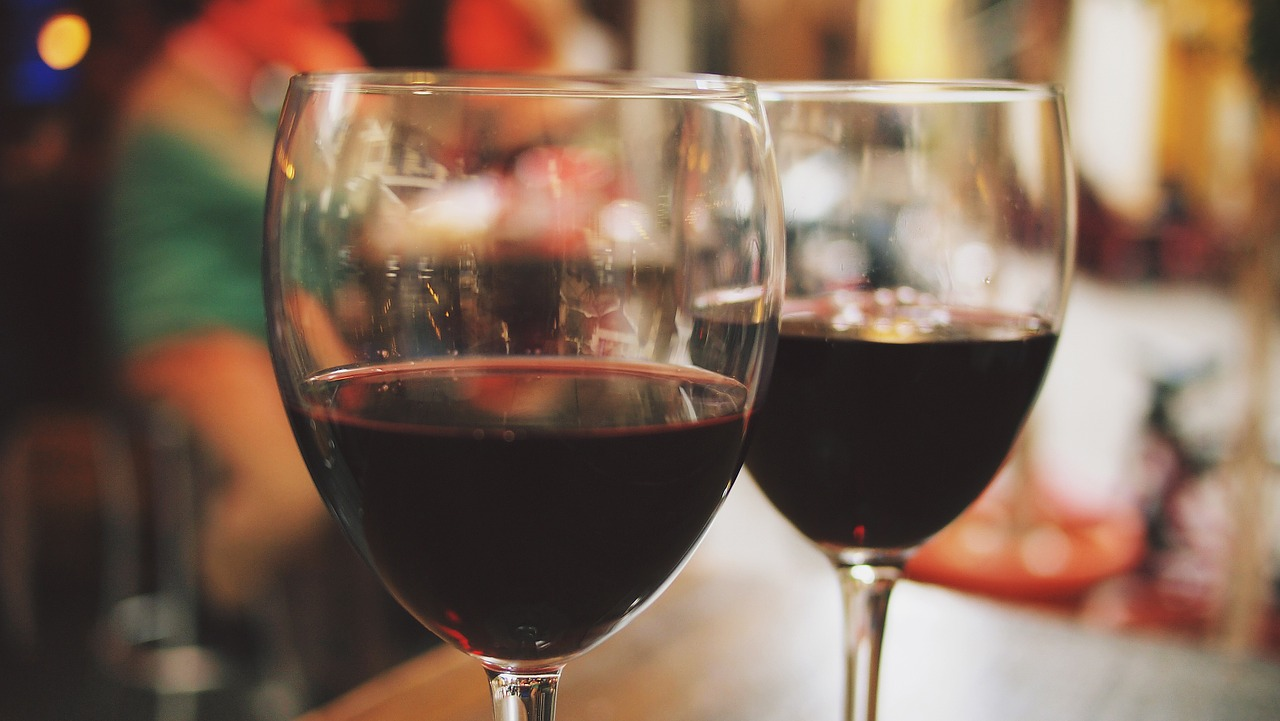 Two clear wine glasses with red wine up close.