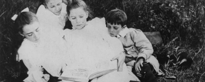Vintage photo of children huddled around one book reading together