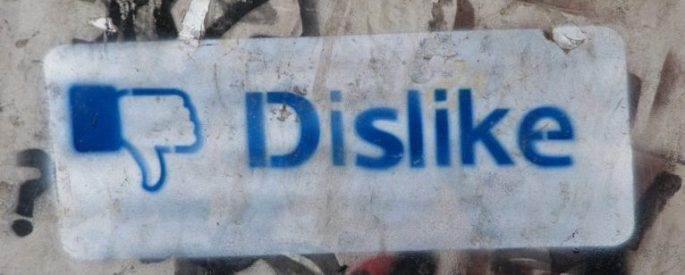 """Graffit on a concrete wall with the Facebook """"Dislike"""" thumbs down"""