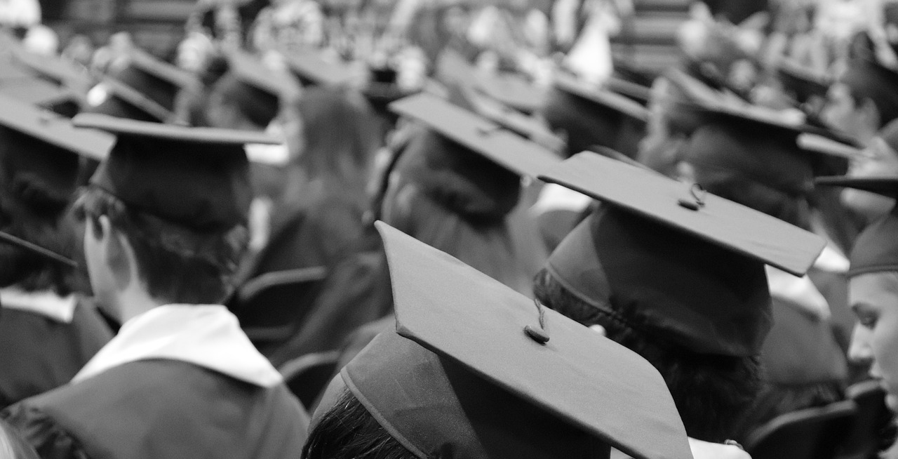 A black and white photo of people sitting with graduation caps on.