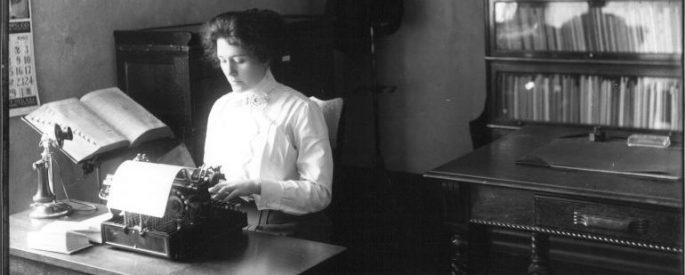 1912 photo of secretary typing at typewriter in front of bookcase