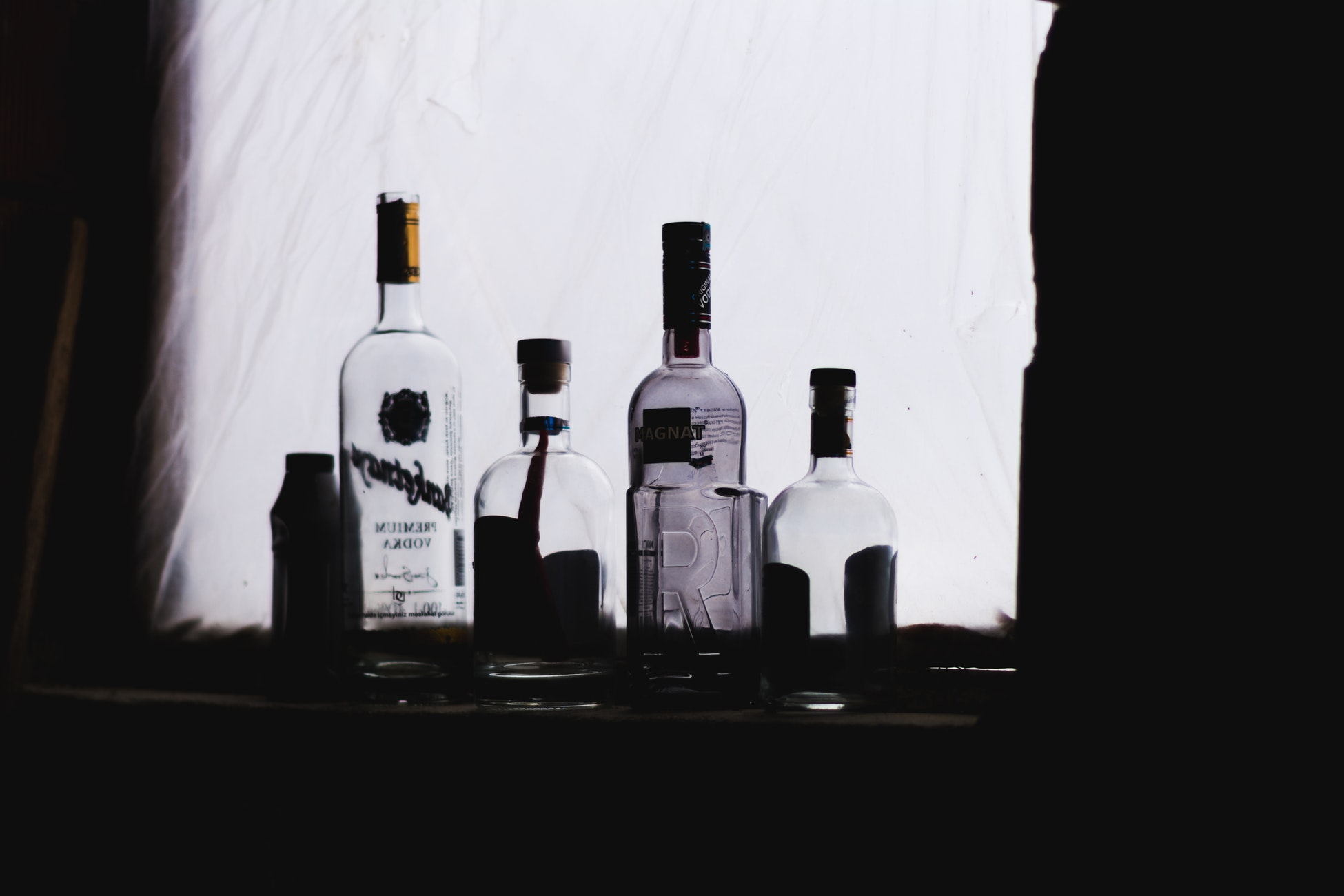 Empty bottles of alcohol on a windowsill backlit.
