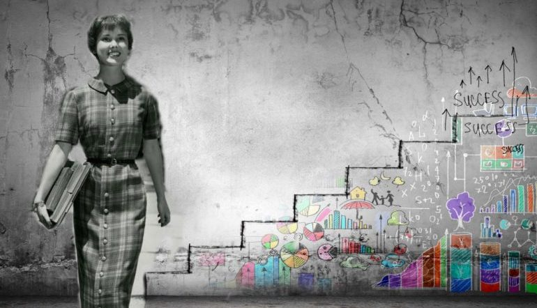 """Woman in black and white standing in front of a wall with a graph to """"success"""" on it"""