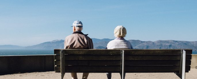 Two older people sitting on a bench with a blue sky above.
