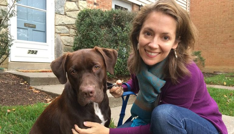 Woman and her chocolate lab posing in front of a house