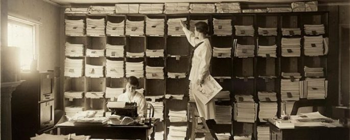 Woman sorting papers in boxes in old publishing company