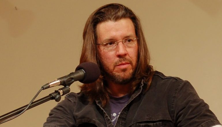 A picture of David Foster Wallace sitting in front of a microphone