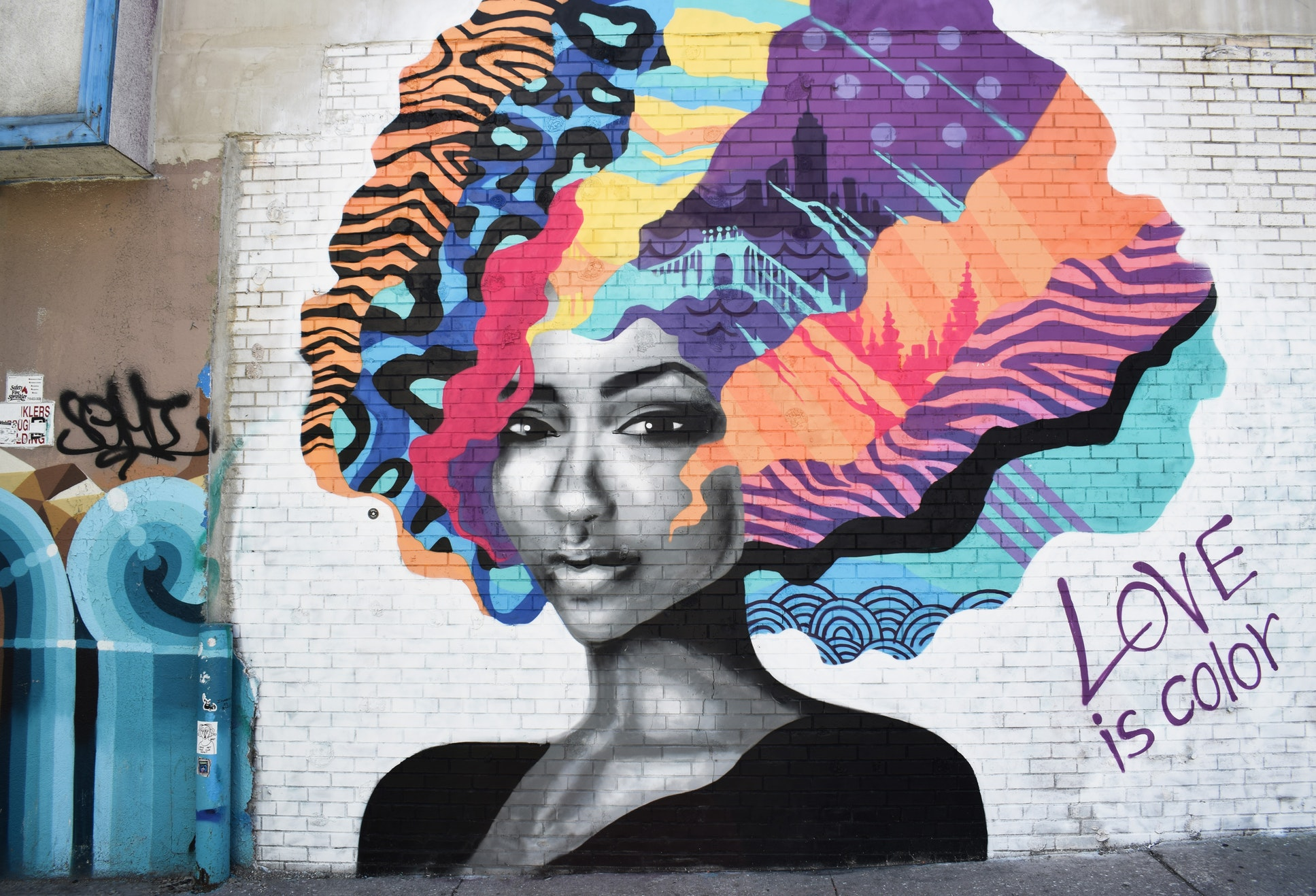 Woman with blue, purple, and pink hair mural on the side fo a white brick building