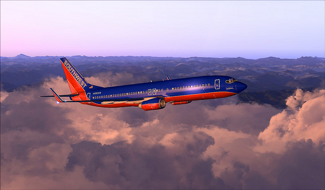 Photo of a blue and red commercial plane flying during dusk in the purple and pink sky