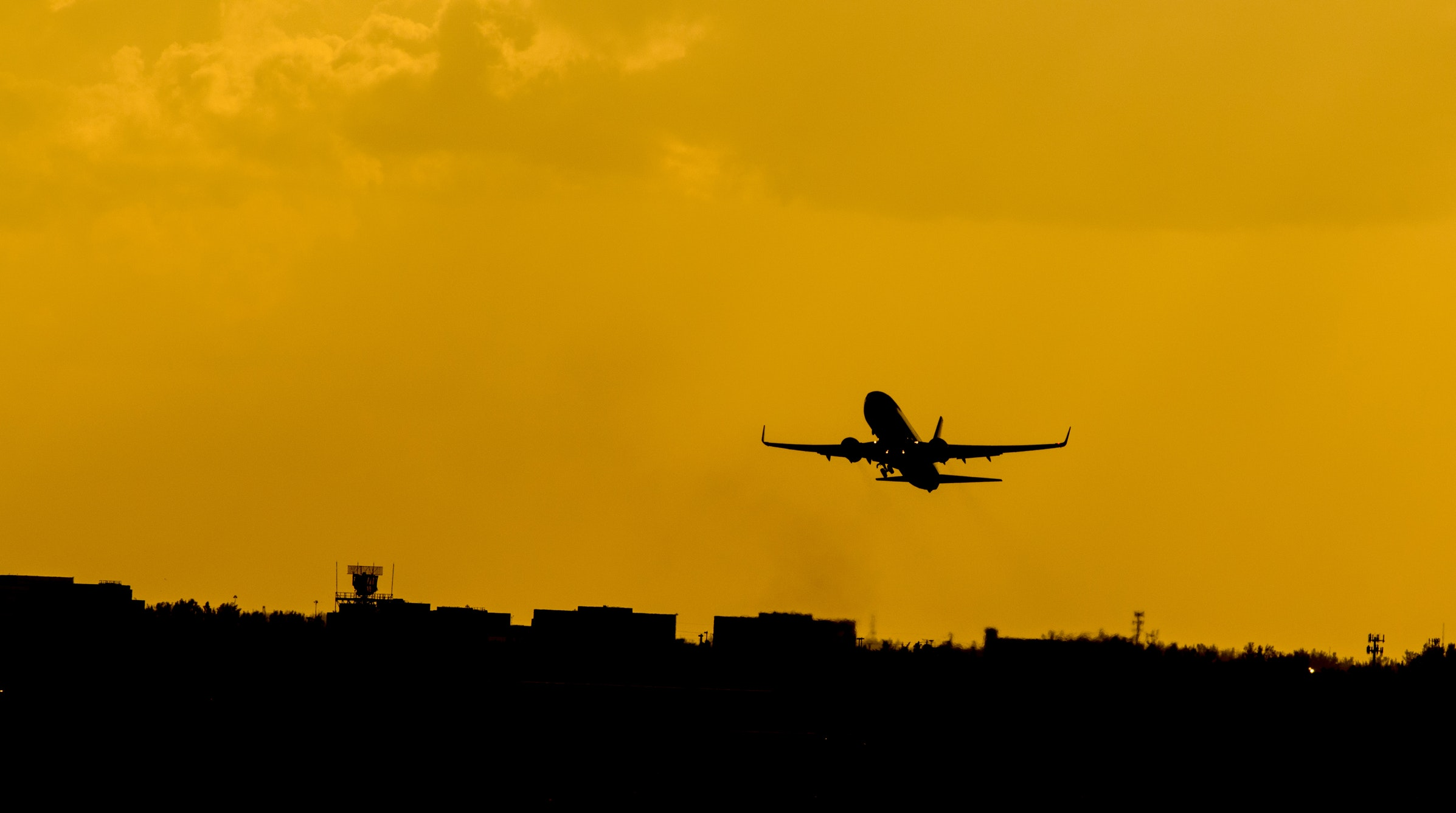Silhouette of a plane flying against a dark yellow sky