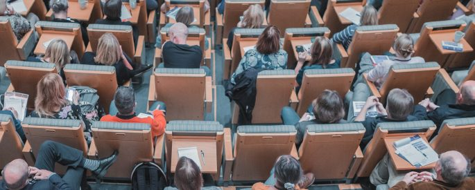 A birds eye view of a lecture hall with people sitting in the chairs.