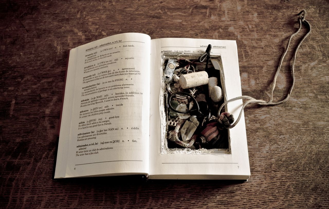 A book lying open that has been hollowed out and filled with small trinkets