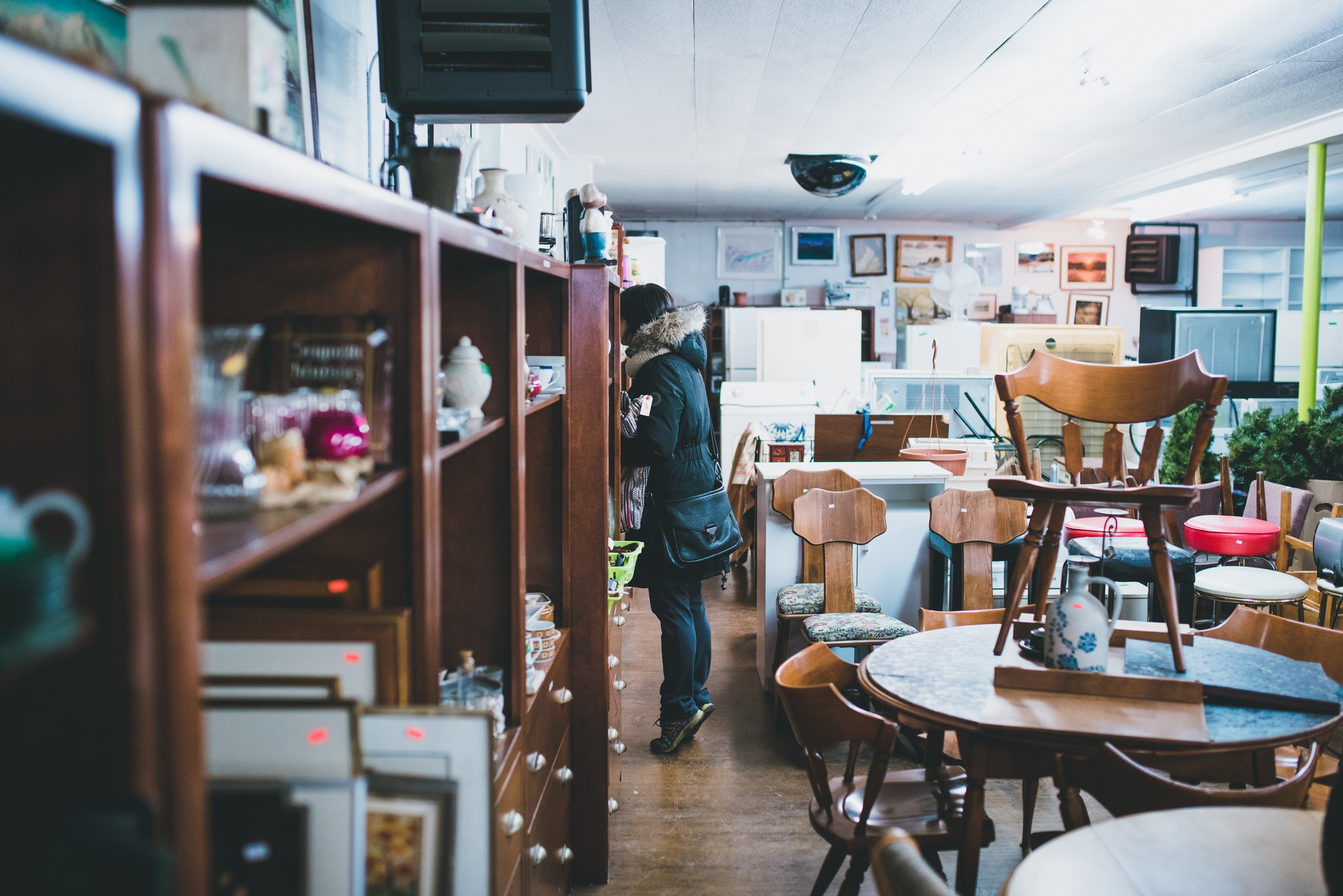 A woman standing in a full thrift shop.