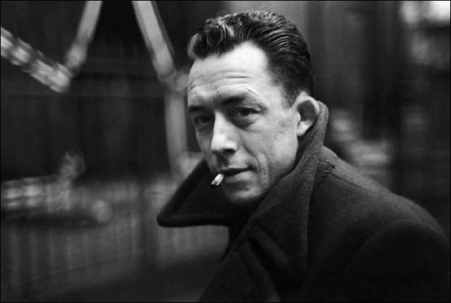 Black and white photo of a man in a coat with a cigarette hanging from his mouth