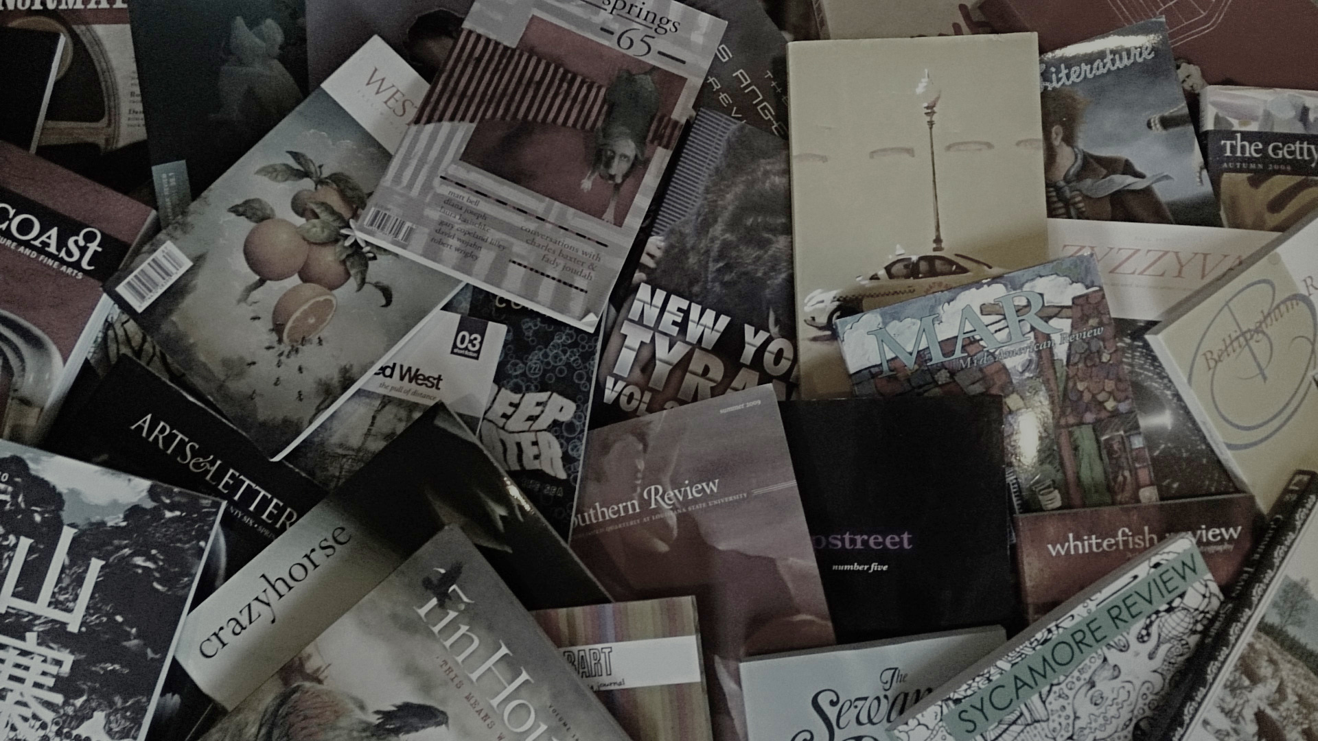 Picture of many different literary magazines sprawled and overlapping on the ground.
