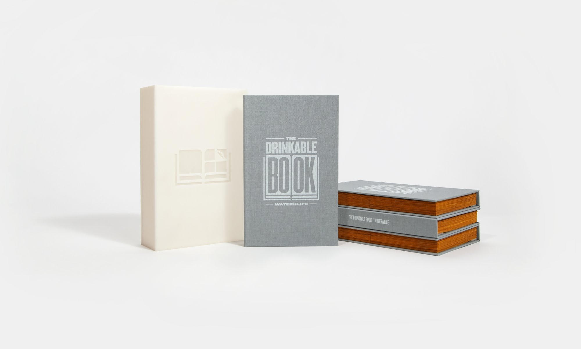 "A stack of ""The Drinkable Book"" sitting on a white background."