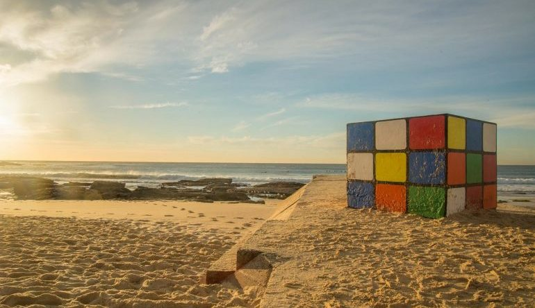 Rubik's Cube partially buried in the sand at the beach