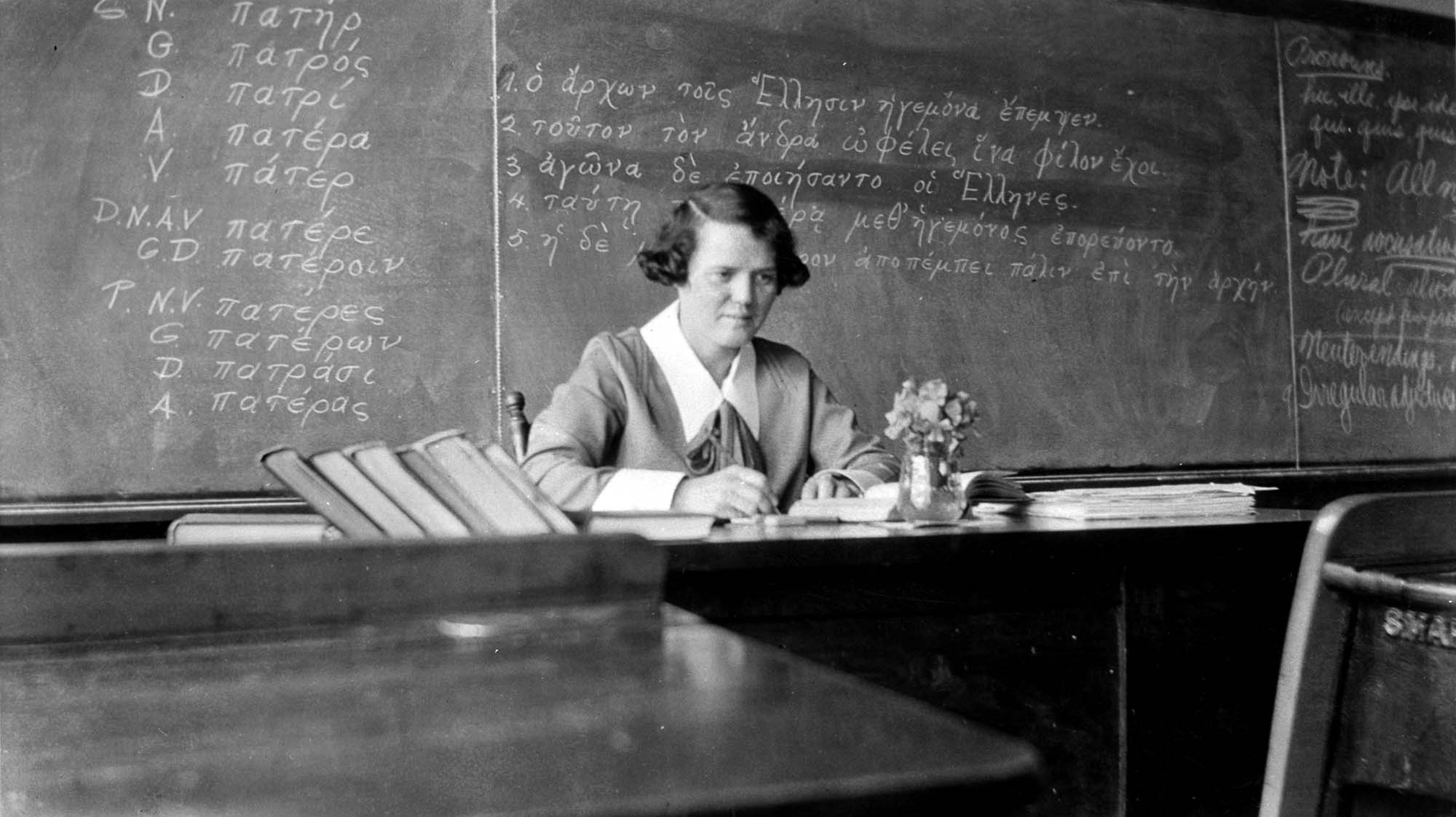 black and white photo of a teacher sitting at her desk