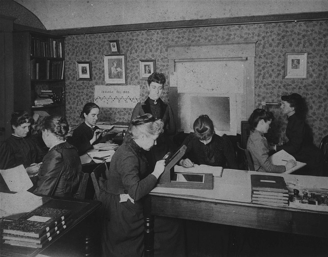 Black and white picture of women in period clothing doing different activities on a sitting room.