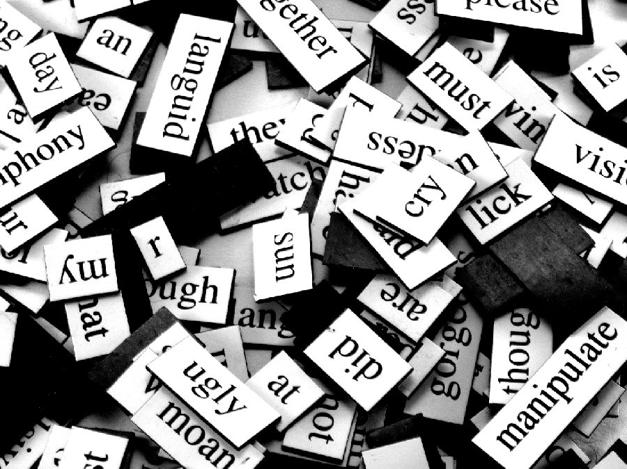 Black and white picture of many overlapping word magnets.