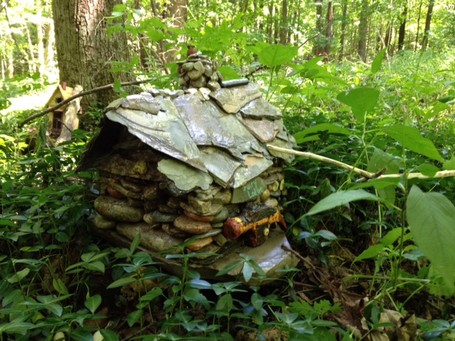 Photo by Marietta Frank of a little house made by different size rocks in the middle of a forest.