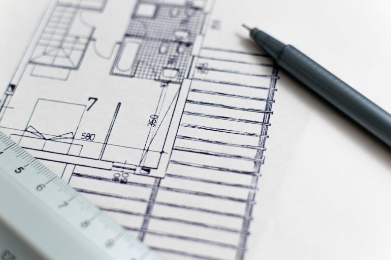 Picture of a pen-drawn house blueprint. On top of the blueprint lies a pen and a ruler.