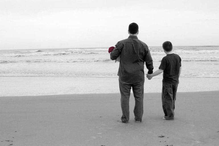 Black and white picture of a man and a boy holding hands on a beach looking away from the camera facing the sea.
