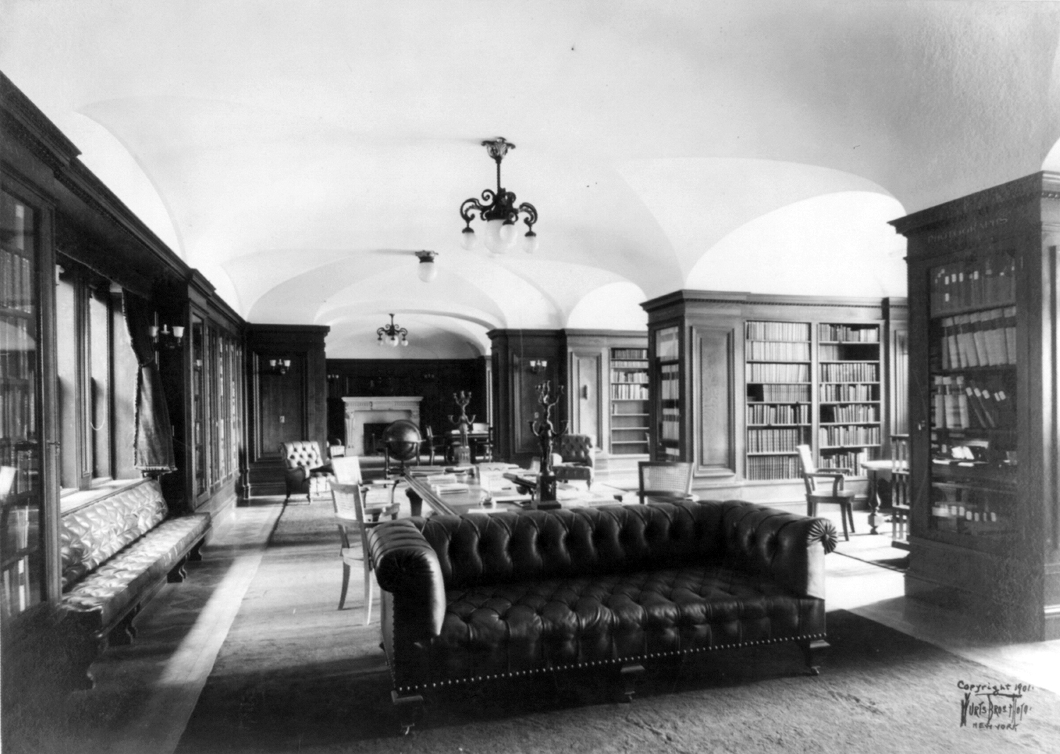 Black and white picture of the interior of a library. There are multiple bookshelves, couches, chairs, and candelabra.