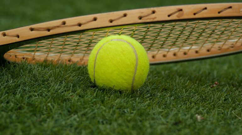 Tennis ball on the grass with a tennis racket lying on top of it.