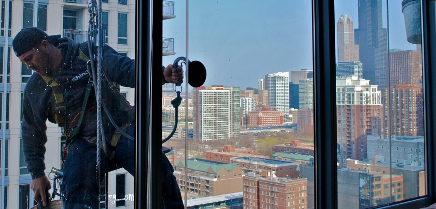 A picture of a window washer taken through the window. In the background you can see a city landscape.