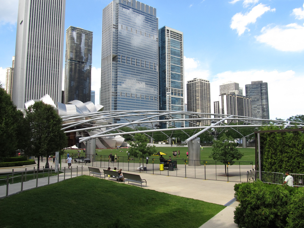 Picture of a city park with some trees and other buildings in the background.