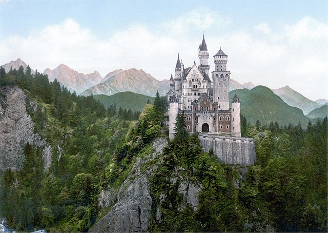 Picture of a castle of a mountain surrounded by trees. There are multiple mountains in the background.