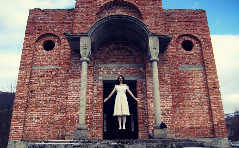 Picture of a woman levitating in front of an old brick building.