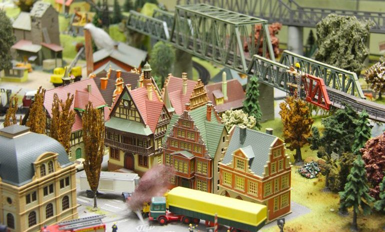 Picture of a colorful miniature city consisting of a couple of houses, bridges, trucks, and other buildings.