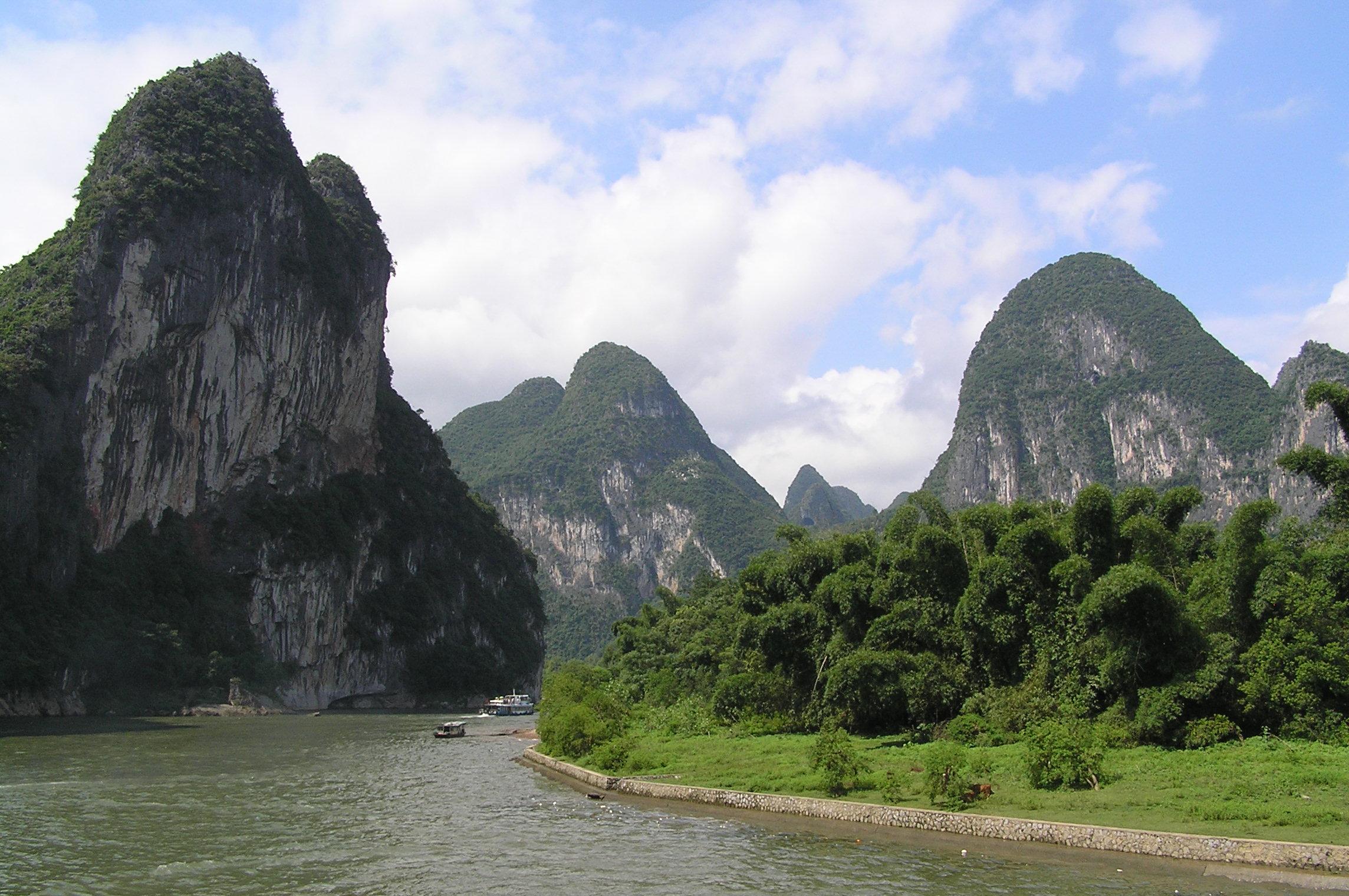 Picture of the Li river going through big mountains full of vegetation. A couple of small boats can be seen on the river.