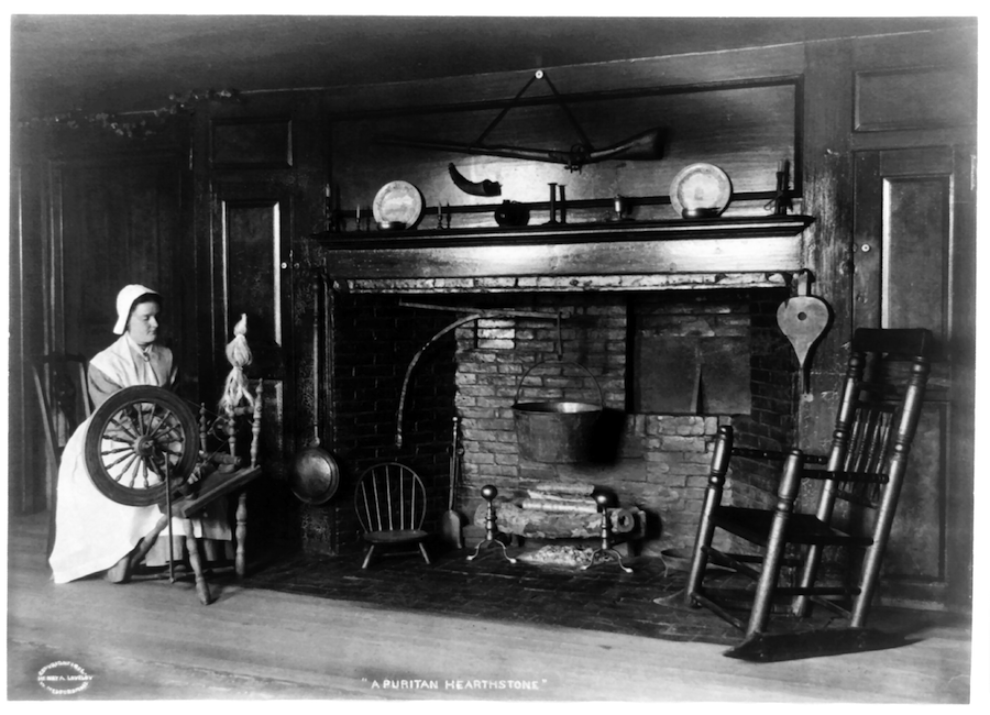 Black and white picture of a woman weaving by a fireplace.